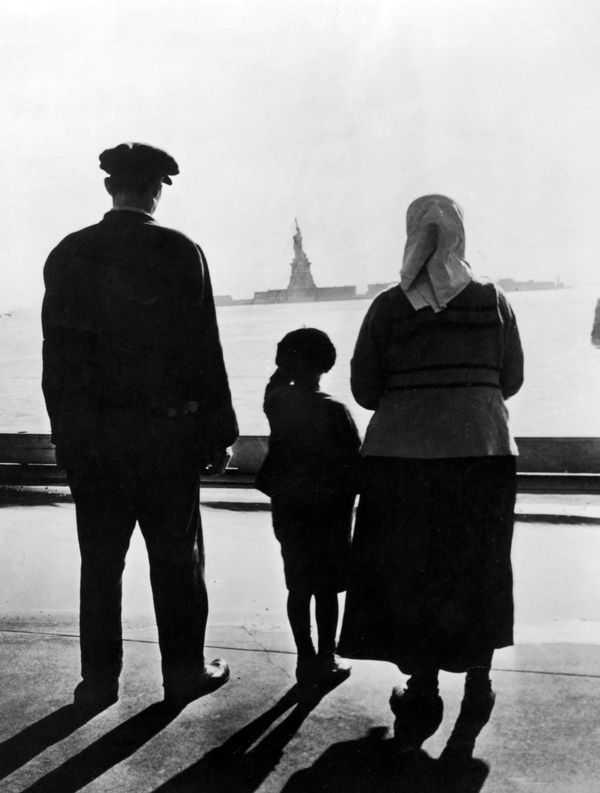 """""""Una familia de inmigrantes contempla la estatua de La Libertad en Nueva York"""". Fuente LesKanaris"""